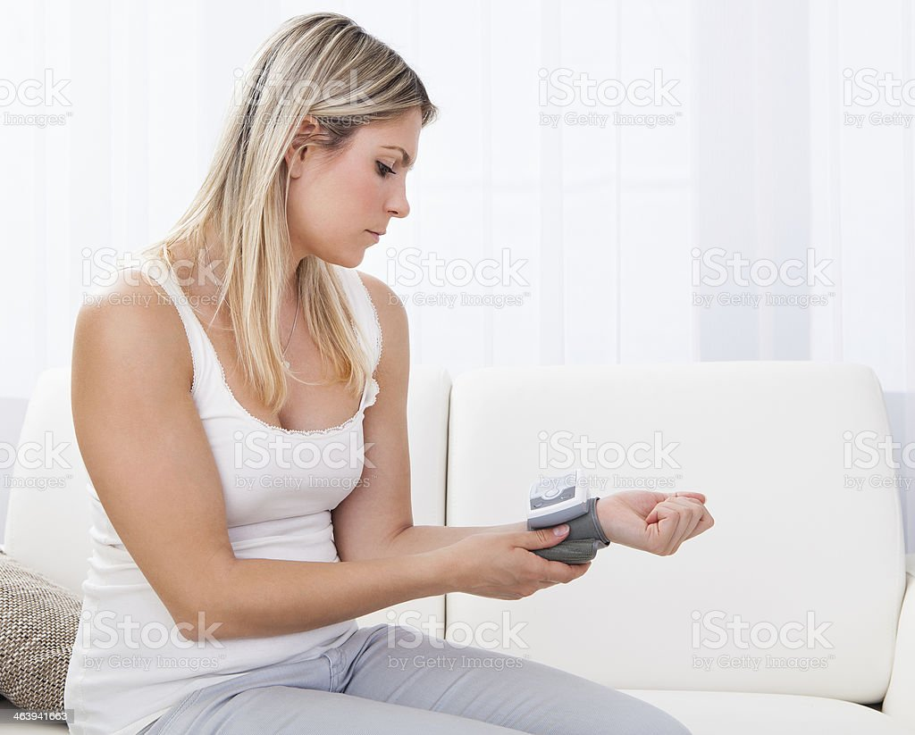 Woman measuring her blood pressure stock photo