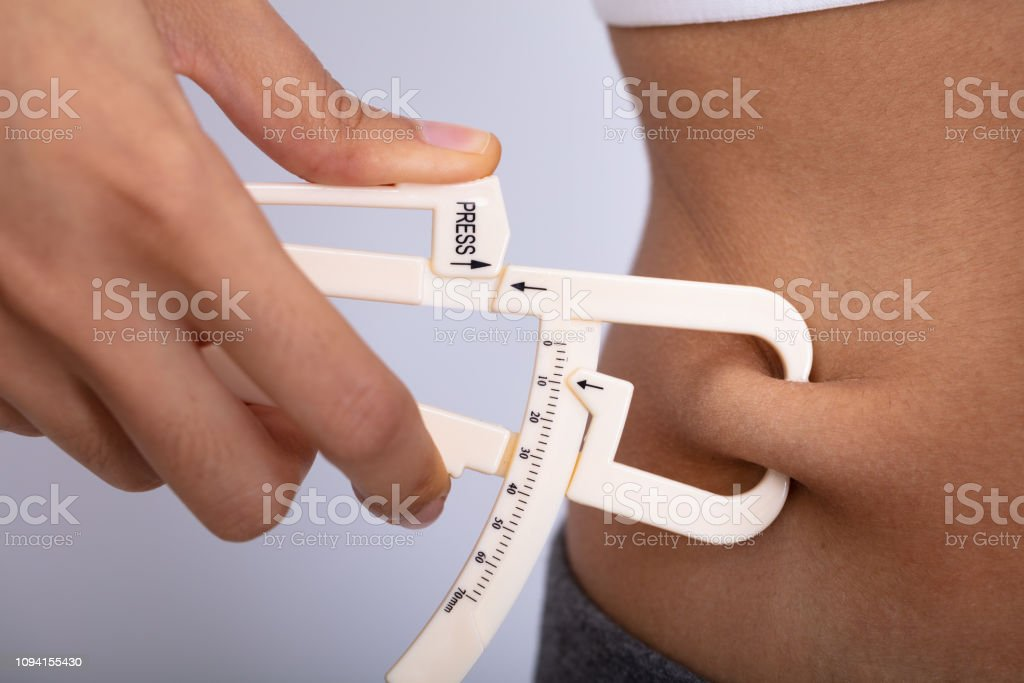 Woman Measuring Her Body Fat With Caliper stock photo