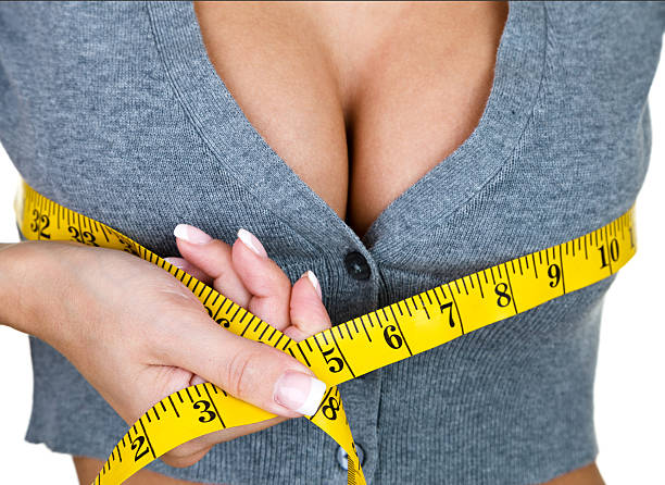 Woman measuring her breast size stock photo