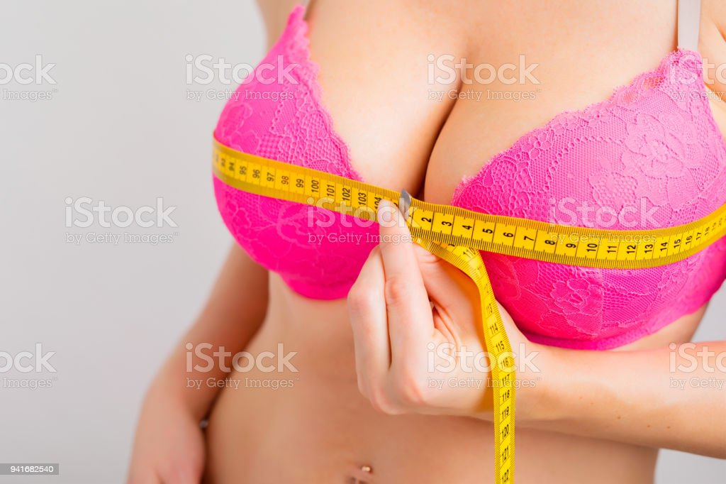Woman measuring her breasts with measurement tape stock photo