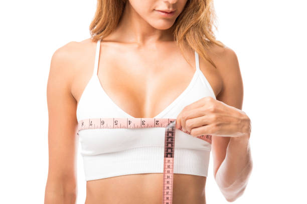 woman measuring her chest size over white background - midsection stock pictures, royalty-free photos & images