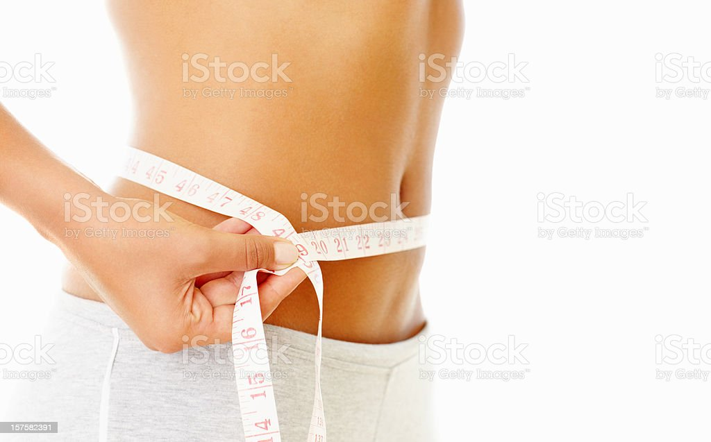 Woman measuring her slim waist with a tape stock photo