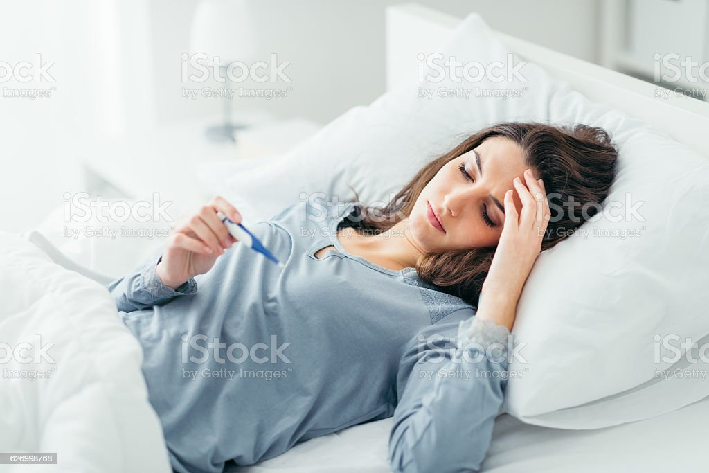 Woman measuring her temperature foto royalty-free