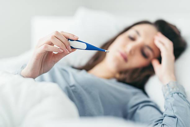 woman measuring her temperature - feber bildbanksfoton och bilder
