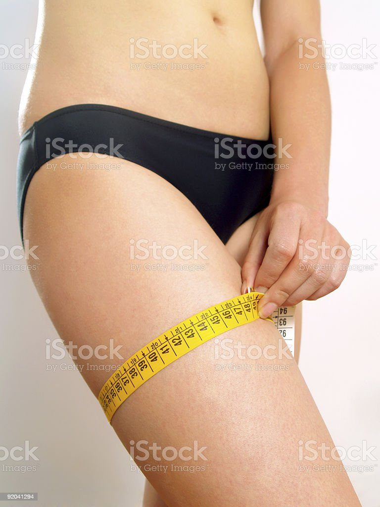 Woman measuring her thigh royalty-free stock photo