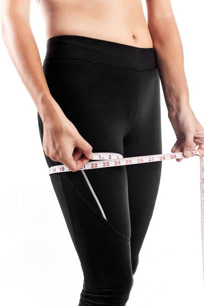 frau messen ihre oberschenkel - damen leggings übergrößen stock-fotos und bilder