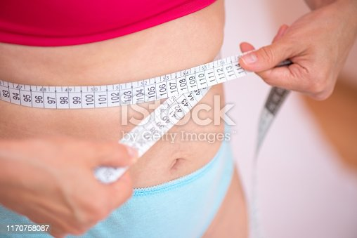 1163494373 istock photo Woman measuring her waist with a centimeter 1170758087