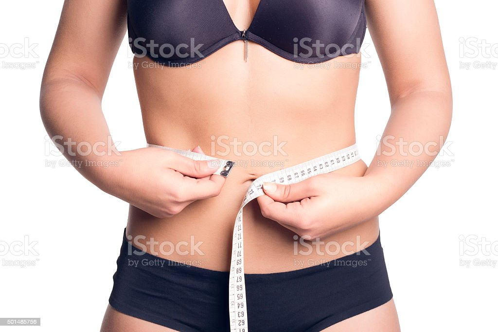 Woman measuring her waist with a measure tape. stock photo