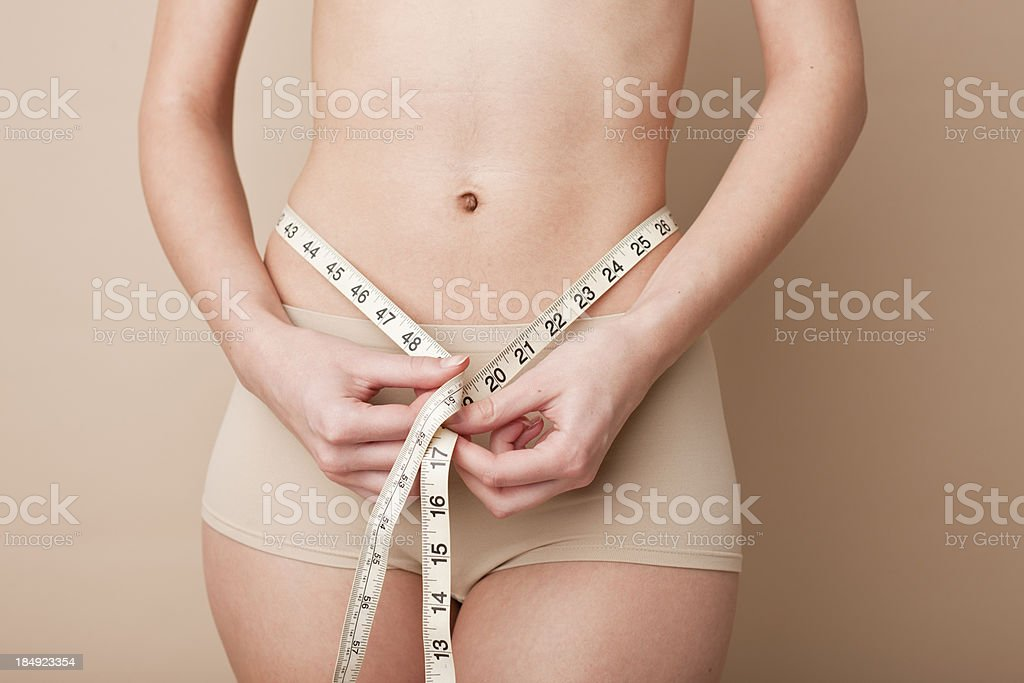 woman measuring herself with measure tape royalty-free stock photo