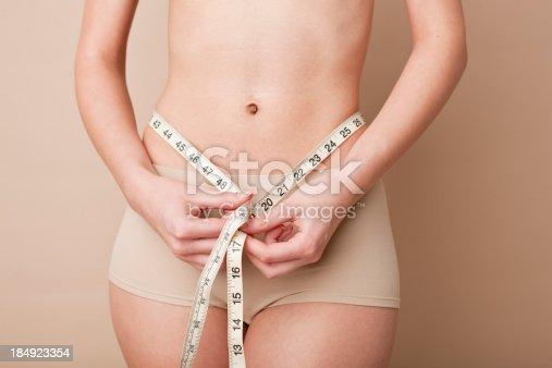 1163494373 istock photo woman measuring herself with measure tape 184923354