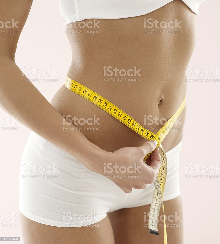 Woman measuring hips with tape measure. royalty-free stock photo