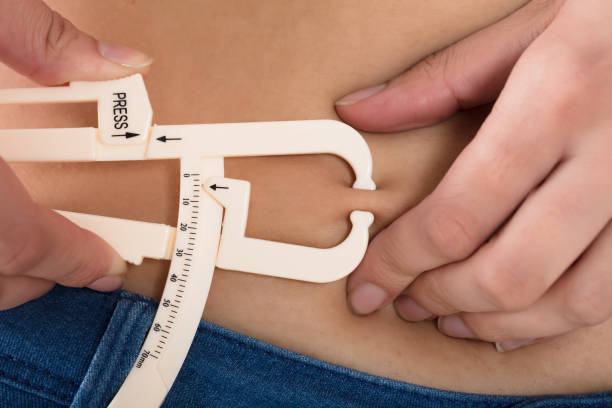 Woman Measuring His Body Fat With Calipers stock photo