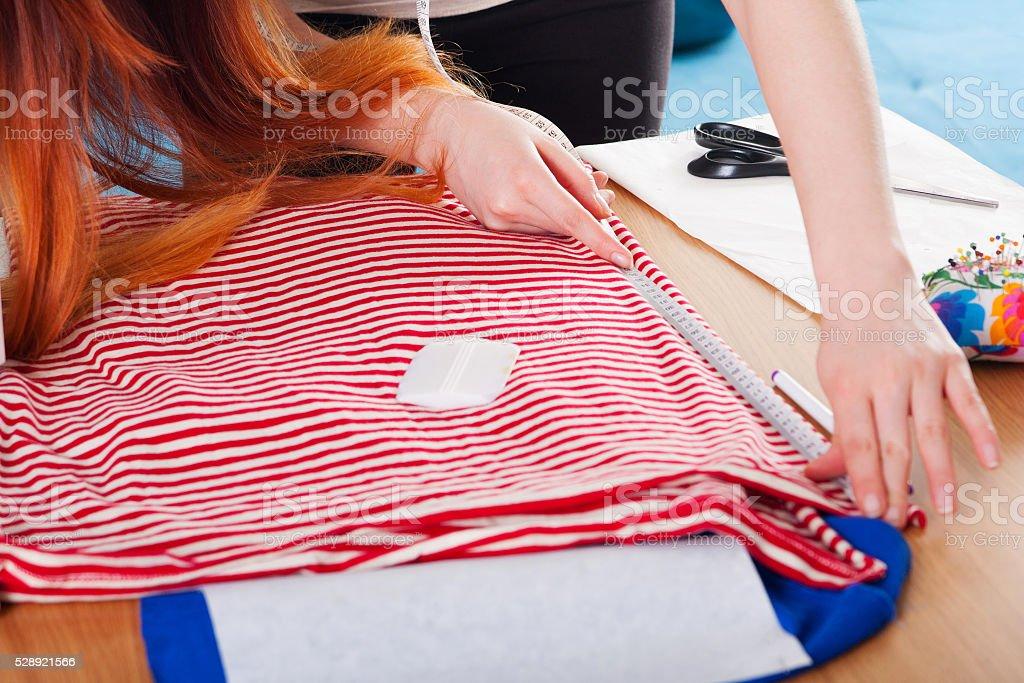 Woman measuring pattern on fabric stock photo