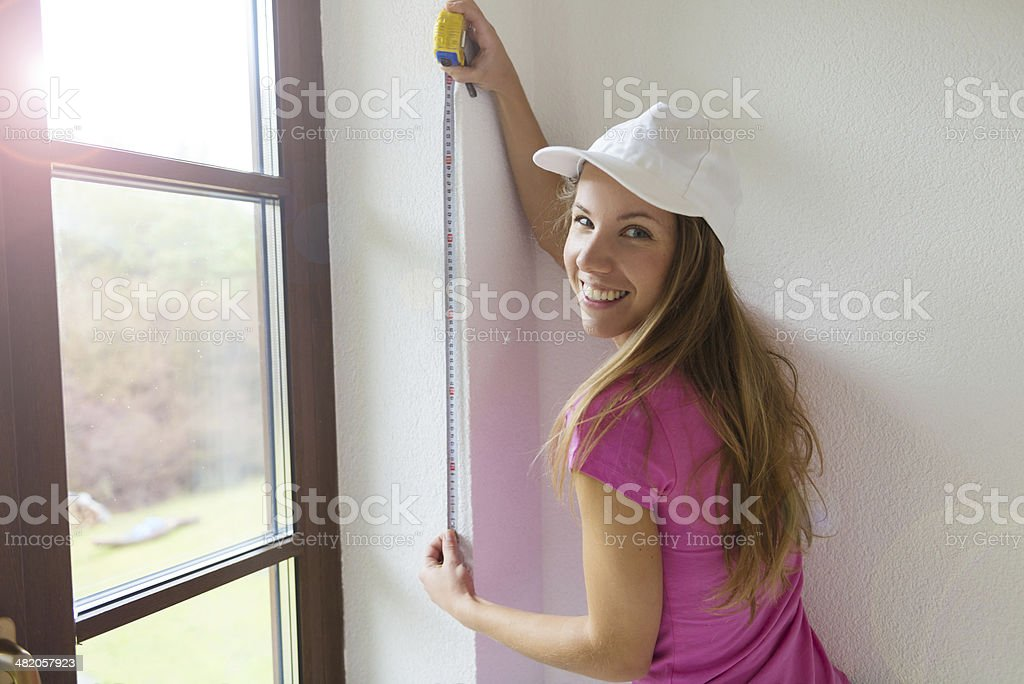 Woman measuring the wall royalty-free stock photo