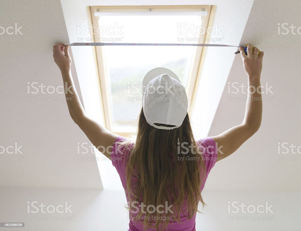 Woman measuring the wall stock photo