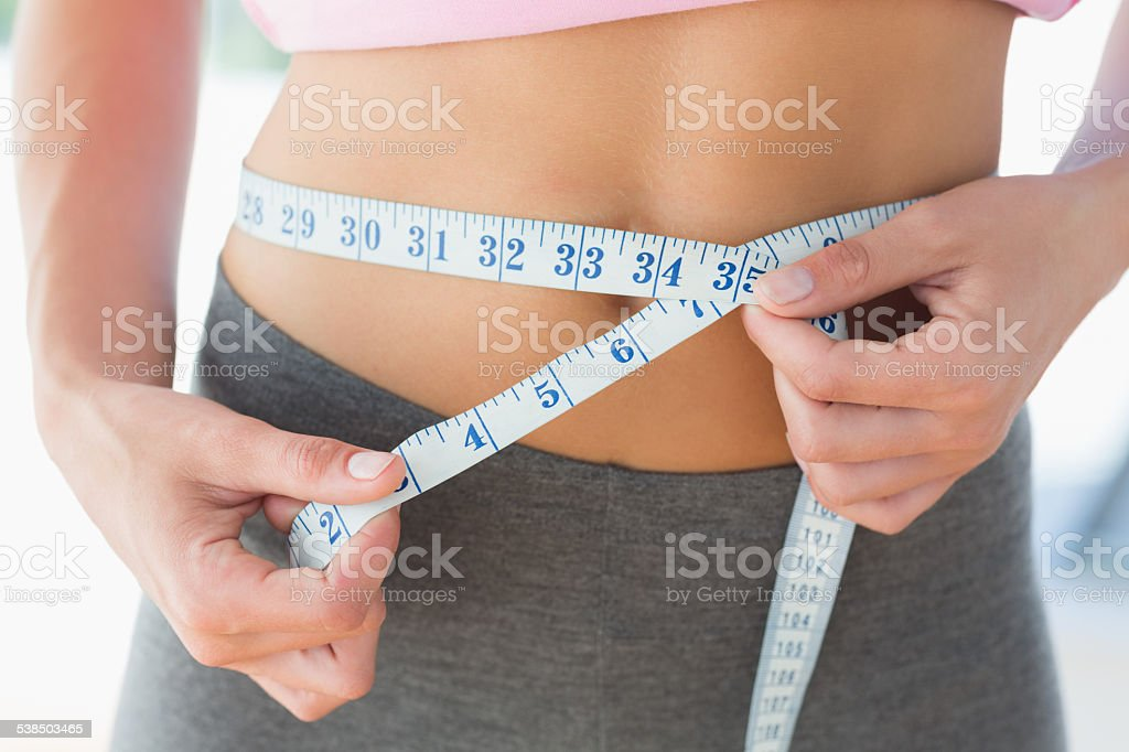 Woman measuring waist in fitness studio stock photo