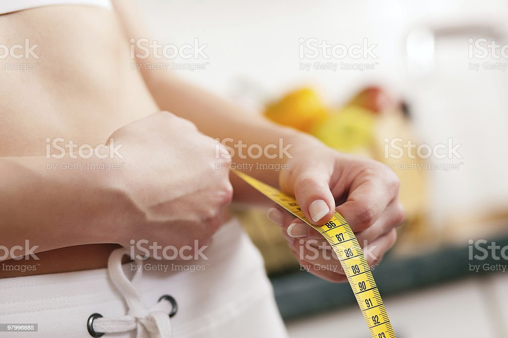 Woman measuring waist with tape royalty free stockfoto