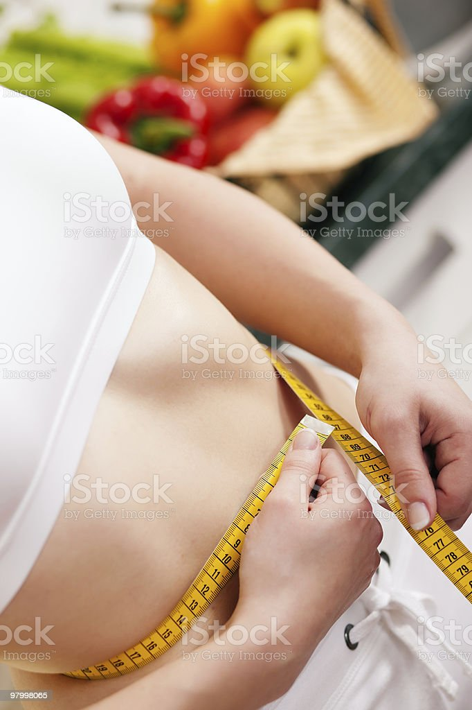 Woman measuring waist with tape royalty-free stock photo