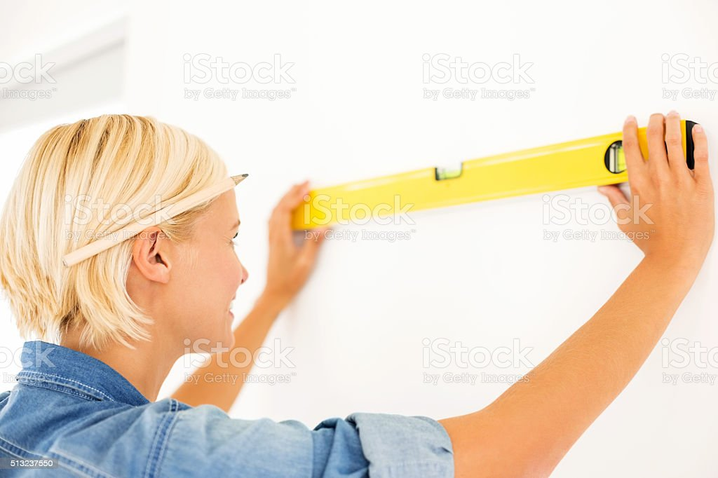 Woman Measuring Wall With Level At Home stock photo