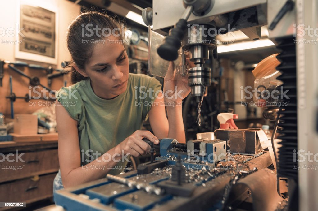 woman mechanic is using a vertical electric dill machine stock photo