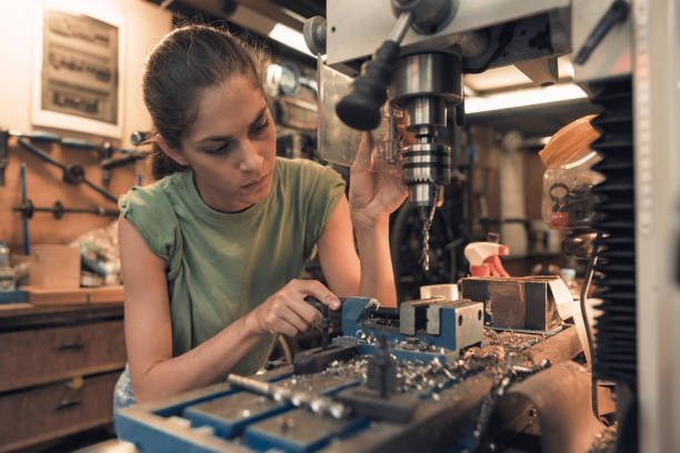 woman mechanic is using a vertical electric dill machine woman mechanic is using a vertical electric dill machine metal worker stock pictures, royalty-free photos & images