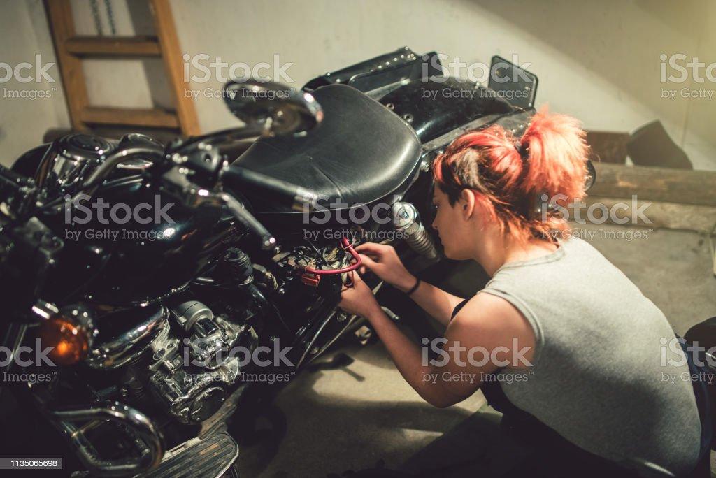 Blonde woman mechanic repair motorcycle in a motorcycle workshop.