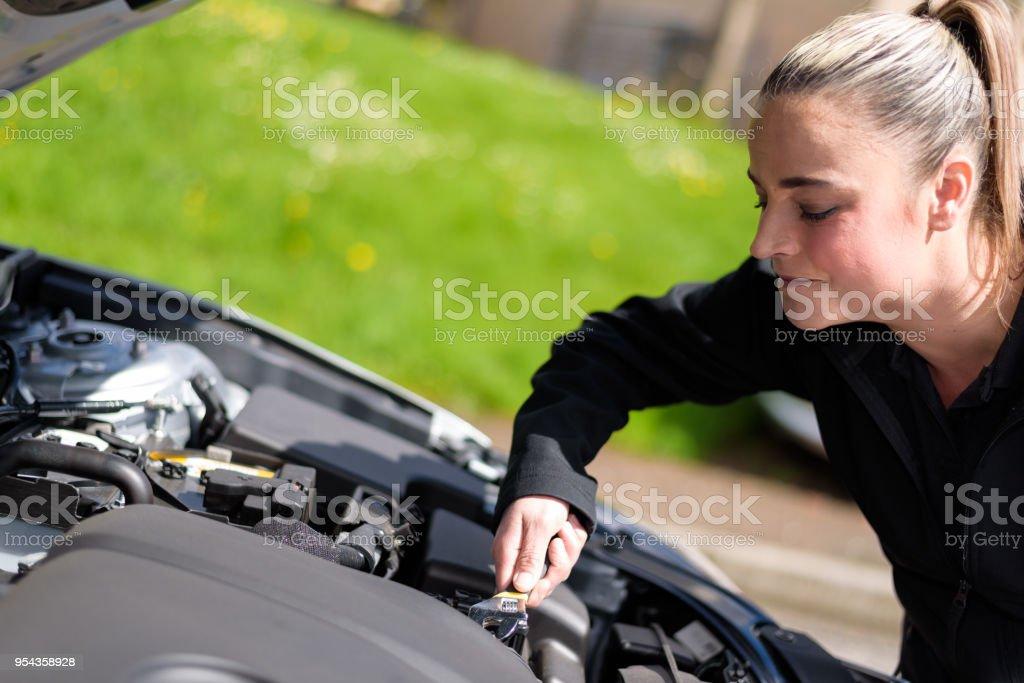 A woman mechanic repairing a car engine at roadside