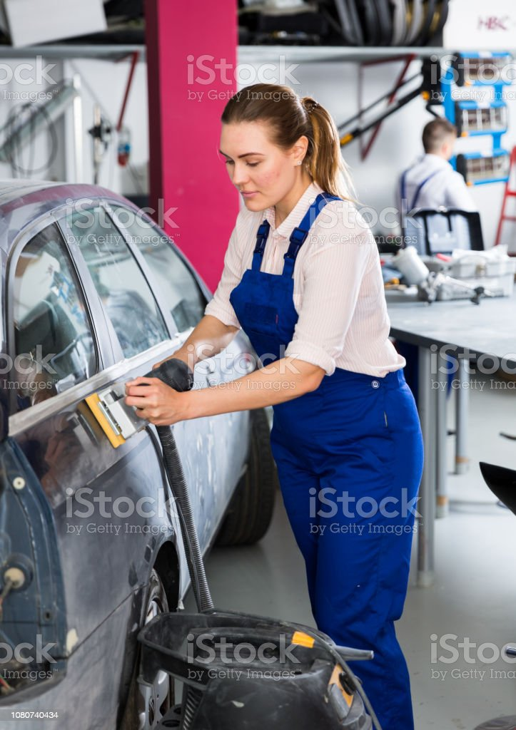 Young woman car mechanic in workshop sanding automobile body,...