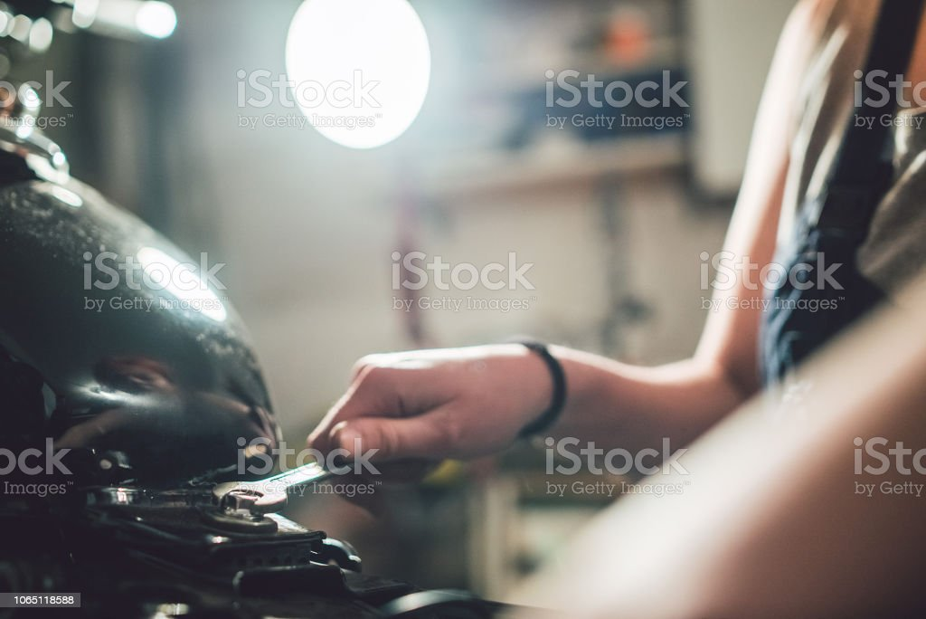 Woman mechanic with wrench in hand attempt to repair motorcycle....