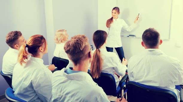 frau medizinstudent erklären, in der nähe von whiteboard - lautsprecher test stock-fotos und bilder