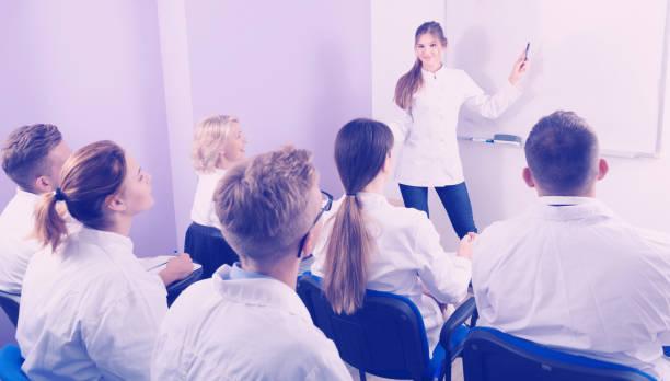 frau medizinstudent einen vortrag in der nähe von whiteboard im auditorium - lautsprecher test stock-fotos und bilder