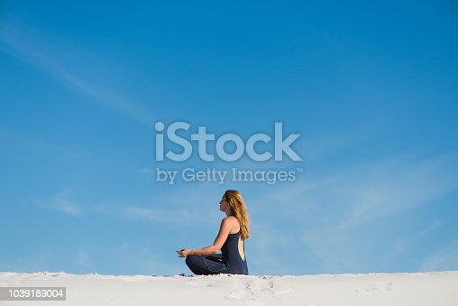istock Woman meditate in the desert sand dunes from back 1039189004