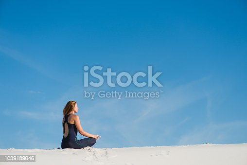 istock Woman meditate in the desert sand dunes from back 1039189046