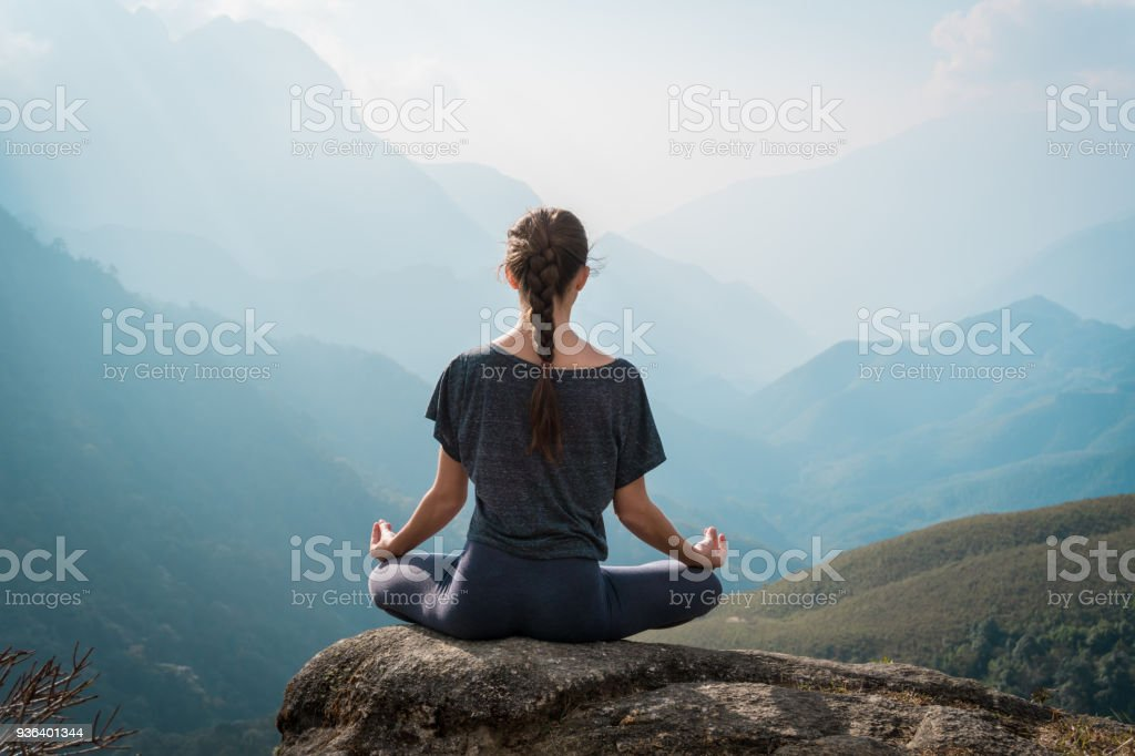 Woman meditates in yoga asana Padmasana stock photo