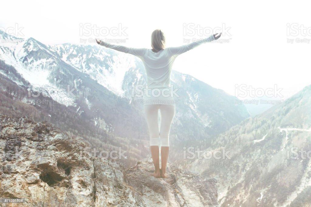 Frau meditiert oben auf der Bergspitze – Foto