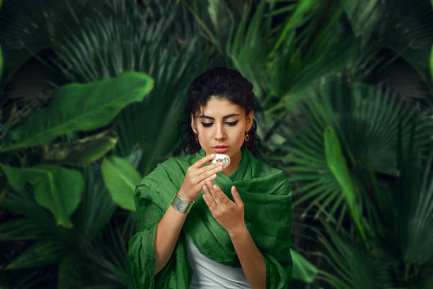 Woman meditating and have tea in tropical rainforest.