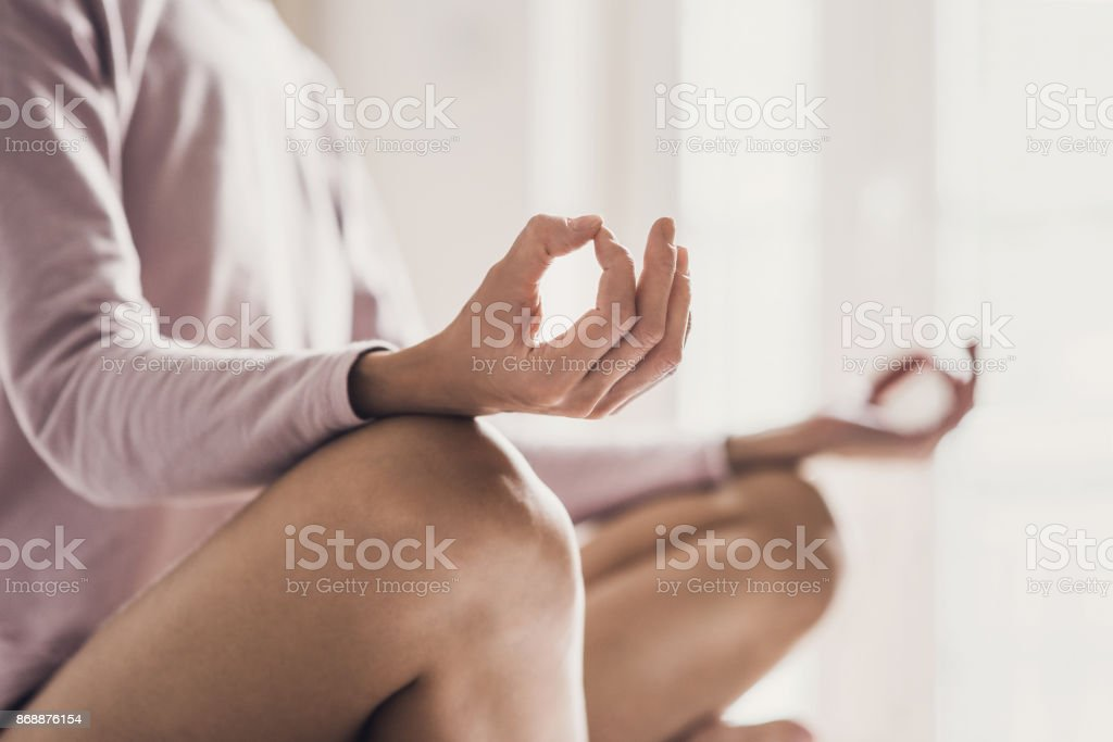 Woman meditating at home. Girl practicing yoga in yoga class stock photo