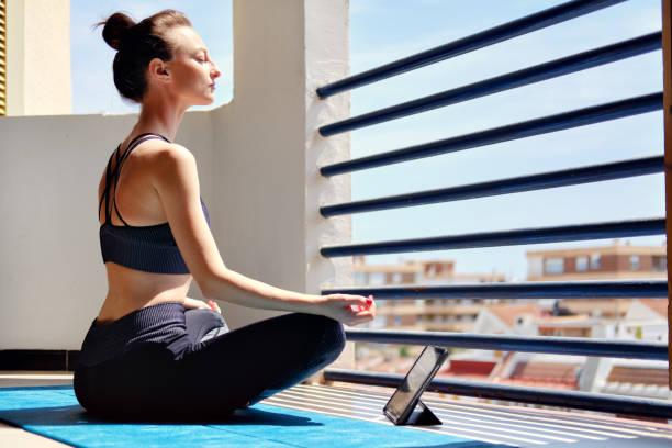 Frau meditiert zu Hause auf Terrasse – Foto