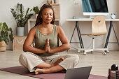 istock Woman meditating at home 1265420974