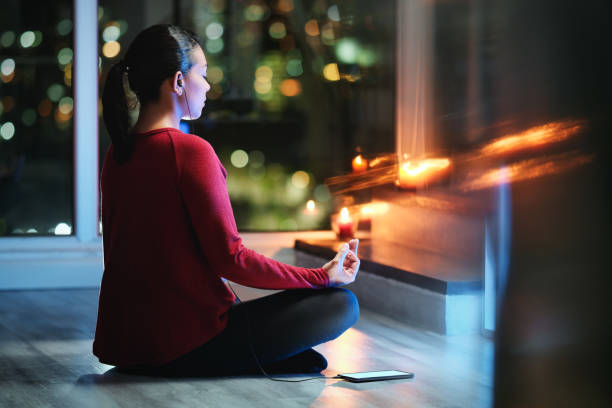 Woman Meditating At Night With Smartphone App For Yoga stock photo
