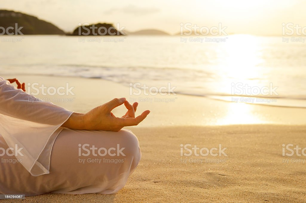 woman meditating at sunset on the Caribbean beach royalty-free stock photo