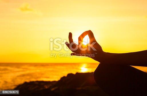 istock Woman meditating at the beach 636260670