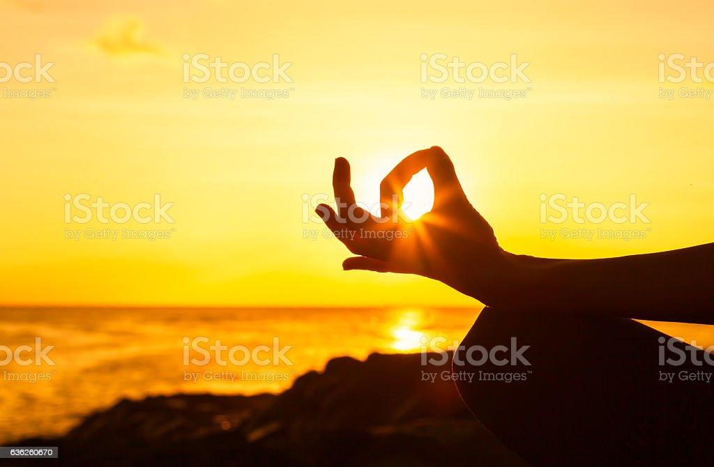 Woman meditating at the beach stock photo