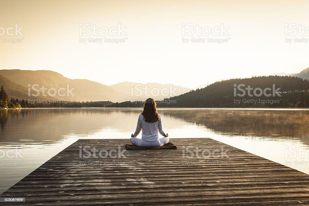 Woman meditating by lake. stock photo