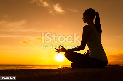 Woman doing meditation practice by the beach.