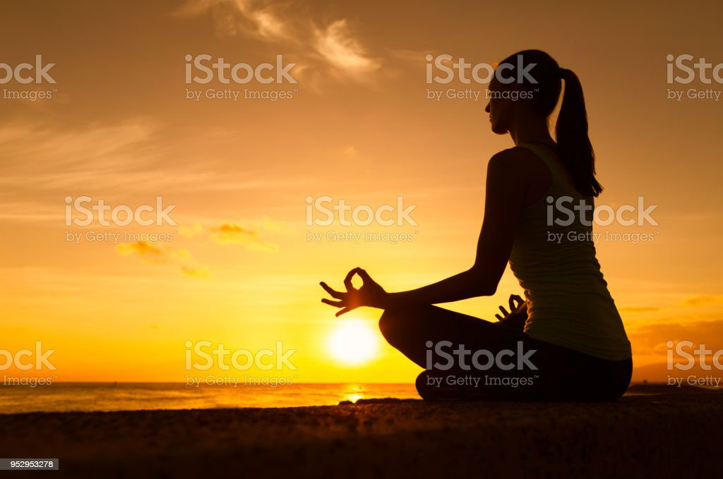 Woman meditating by the beach stock photo