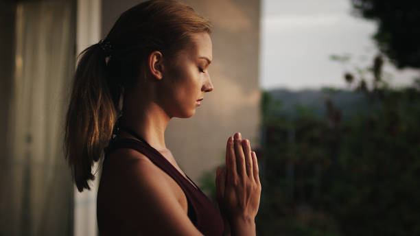 Woman meditating by the pool stock photo