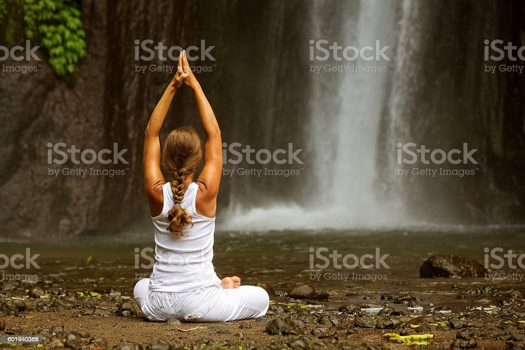 woman meditating doing yoga between waterfalls stock photo