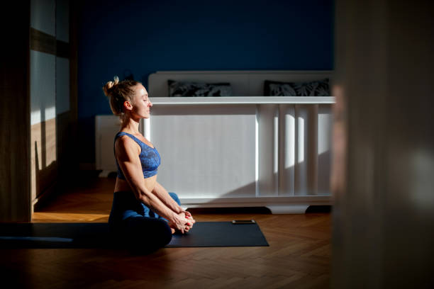 Woman meditating in bound angle pose stock photo