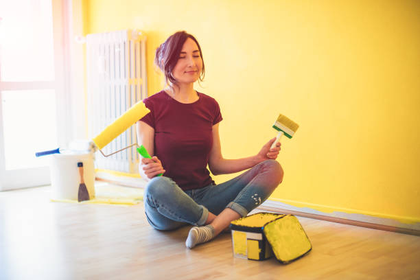 Woman meditating in front of an open can of yellow paint, holding a roller and brush in her hands - hobby, dye and renovation concept